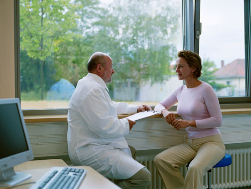 A woman consulting with her oral surgeon about her upcoming oral surgery.