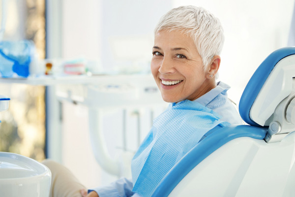 Smiling woman with short white hair sitting in a dental chair